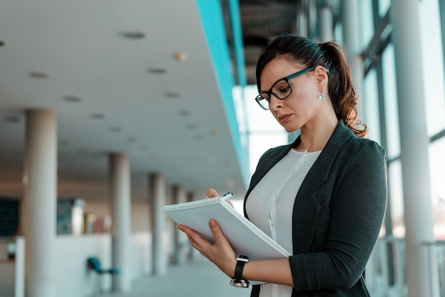 Businesswoman signing documents in office lobby. Premium Photo
