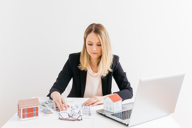 Businesswoman siting in front of laptop looking at blueprint at office Free Photo