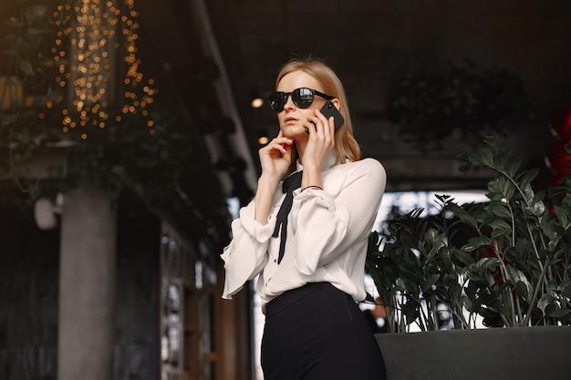 電話でテーブルに座っている女性実業家 無料写真