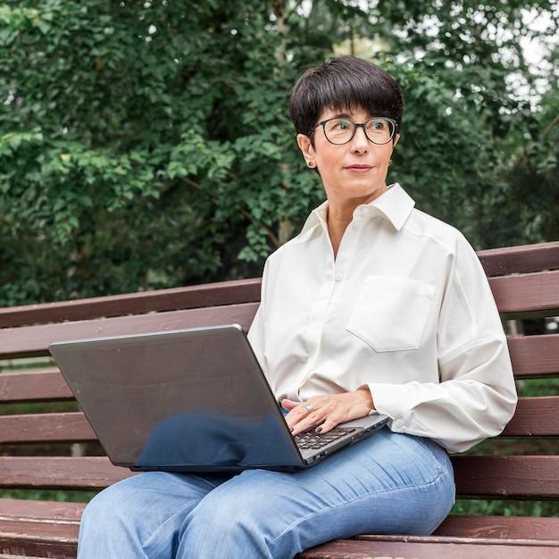 Imprenditrice seduta su una panchina e guardando lontano Foto Gratuite