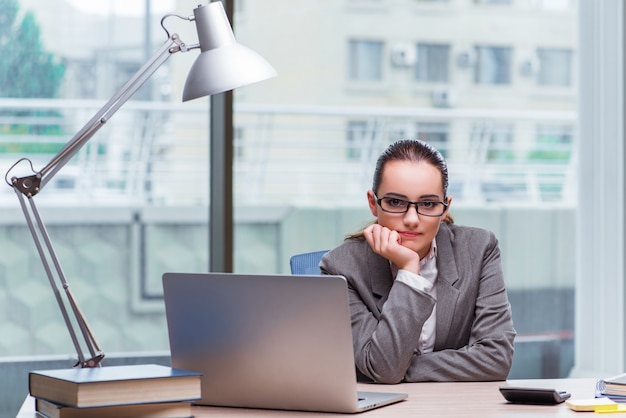 Businesswoman sitting at her desk in business concept Premium Photo