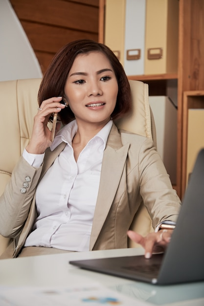 Businesswoman speaking on phone in office Free Photo