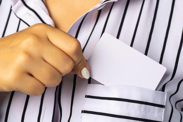 Бизнесвумен достает белую визитку из кармана блузки. Premium Фотографии