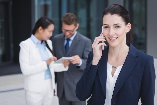 Businesswoman talking on mobile phone Free Photo