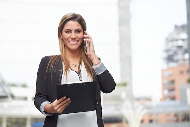 Businesswoman talking to mobile in urban environment Premium Photo
