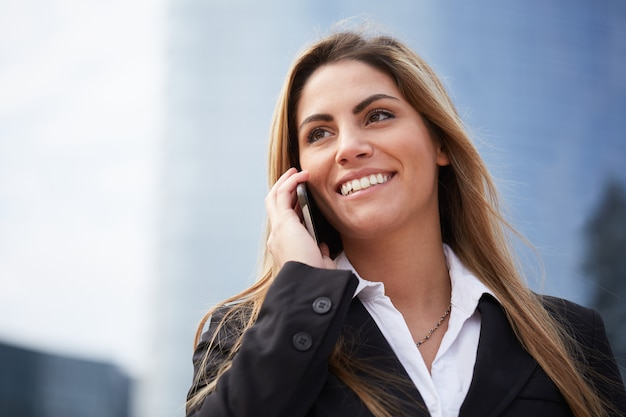 Businesswoman talking to mobile in urban environment Premium Photo