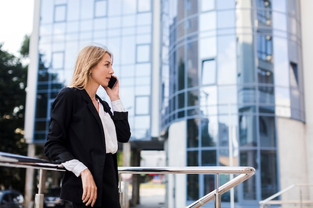 Businesswoman talking on the phone in front of a building Free Photo