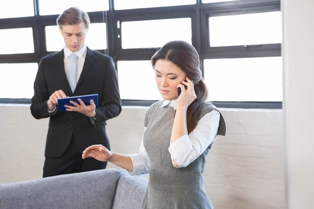 Businesswoman talking on smartphone and businessman using digital tablet in office Premium Photo