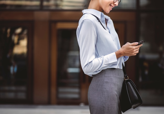 Businesswoman texting on her phone Free Photo