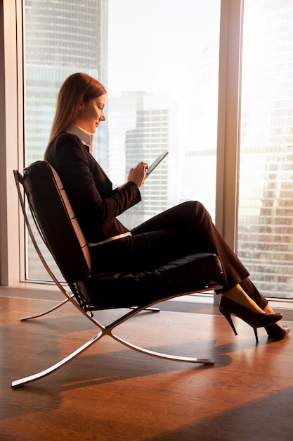 Businesswoman using digital tablet in hotel room Free Photo