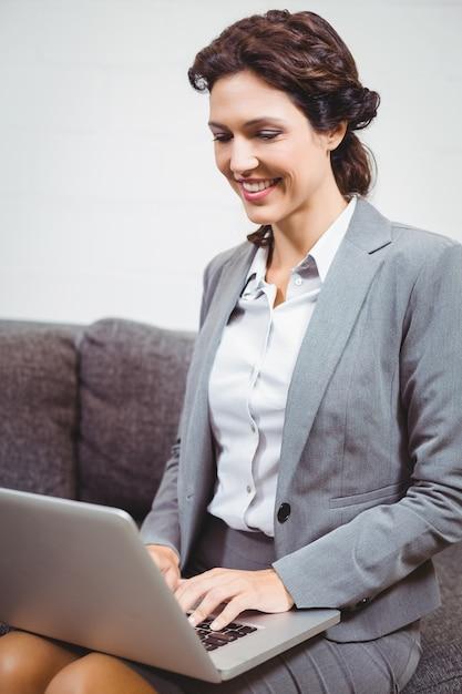 Businesswoman using laptop on sofa Premium Photo