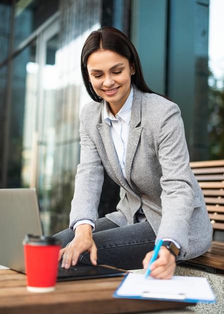 屋外でコーヒーを飲みながらノートパソコンを使用して実業家 無料写真