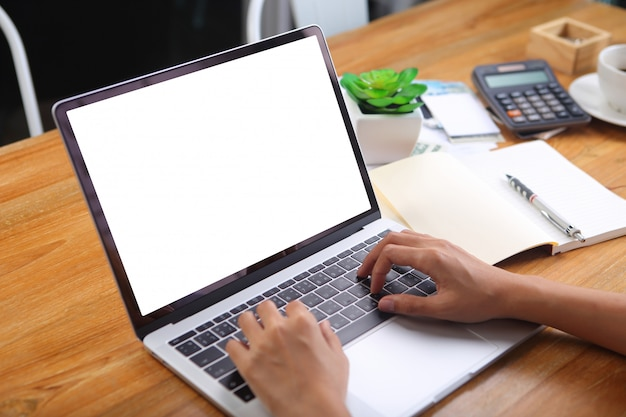 Businesswoman using mockup laptop with office stationery on wooden desk Premium Photo