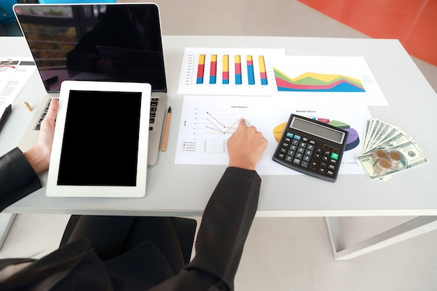 Businesswoman using tablet and computer while working on  company summary report with graph Premium Photo