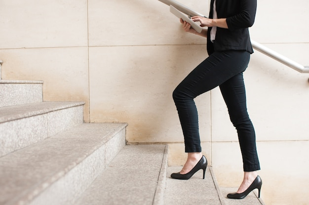 Businesswoman walking upstairs and using touchpad Free Photo