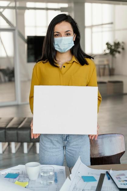 Деловая женщина в медицинской маске с пустой картой Бесплатные Фотографии