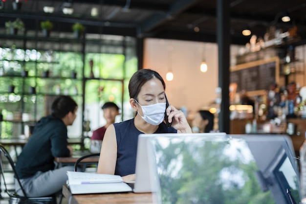 Businesswoman wearing face mask talking on cell phone working on laptop. Premium Photo