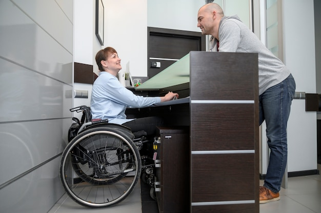 Businesswoman in wheelchair and man long view Free Photo