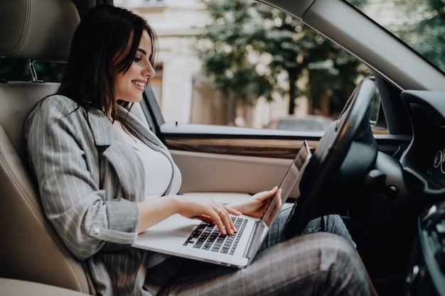 Imprenditrice con un laptop nella sua auto in strada Foto Gratuite