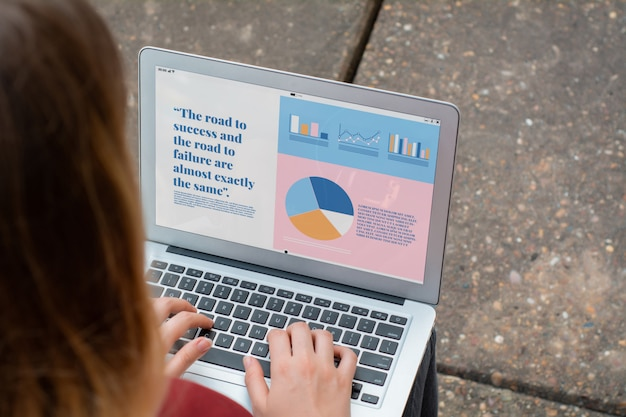 Businesswoman with laptop showing statistics about company growth Premium Photo