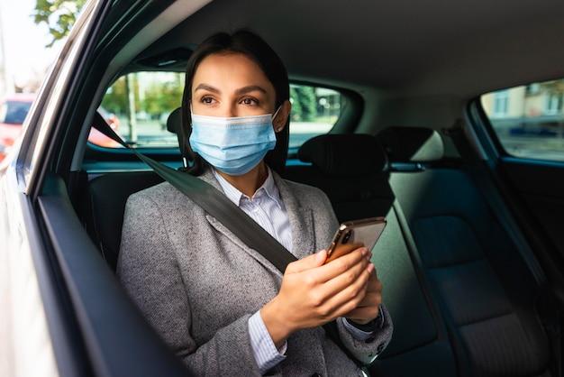 車の中で医療マスクとスマートフォンを持つ実業家 Premium写真