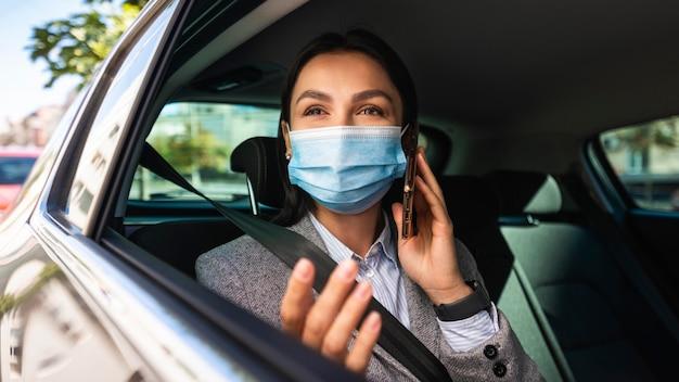 車の中で電話で話している医療マスクを持つ実業家 Premium写真