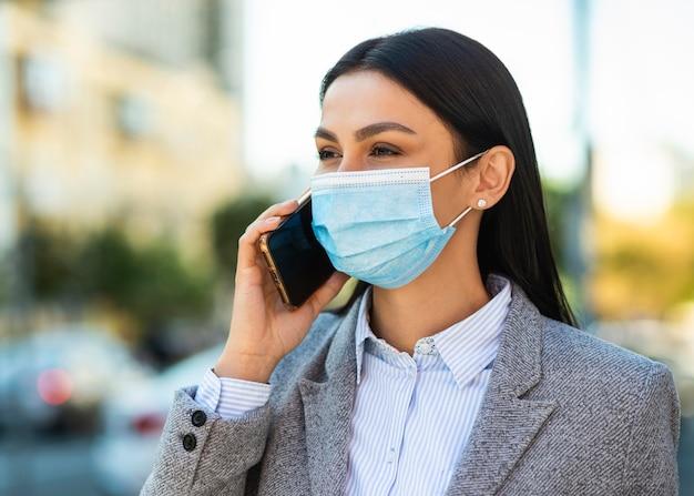 電話で話している医療マスクを持つ実業家 Premium写真