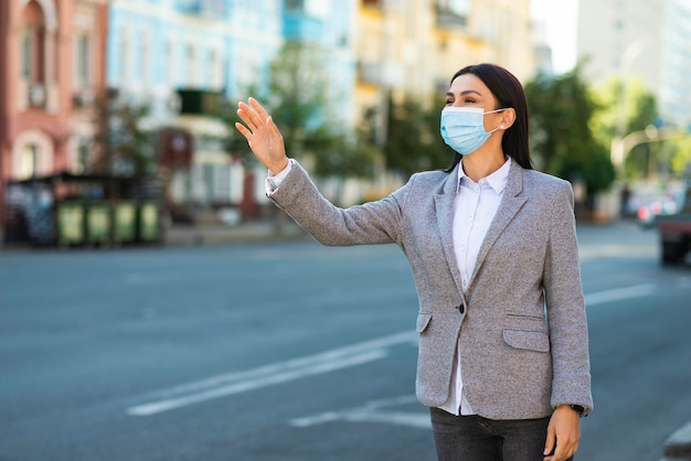 Деловая женщина с медицинской маской машет на улице Premium Фотографии