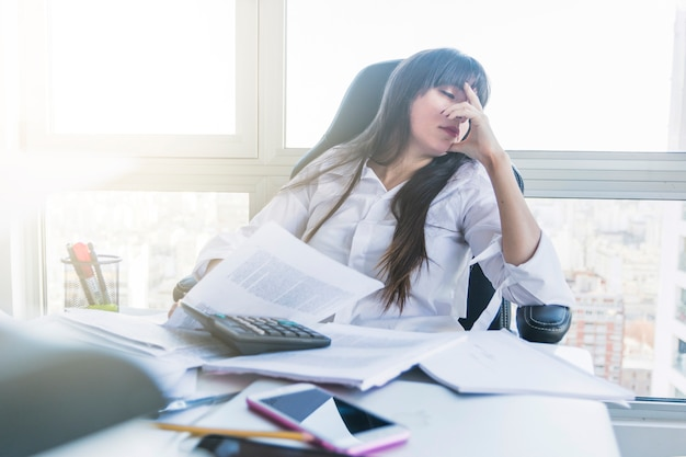 Businesswoman with messy desk sleeping in the office Free Photo