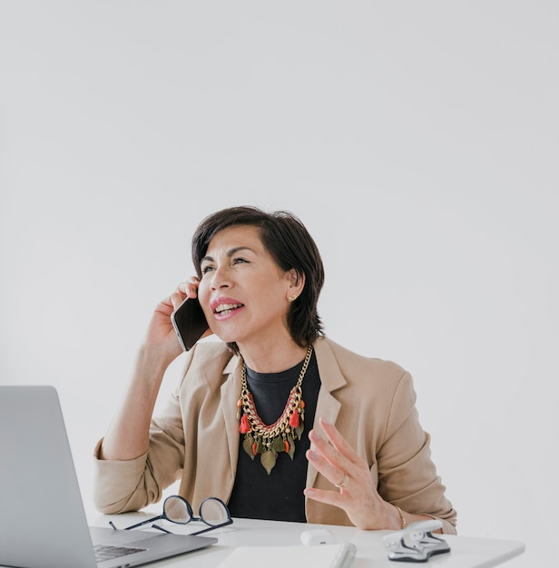 Businesswoman with necklace talking on the phone Free Photo