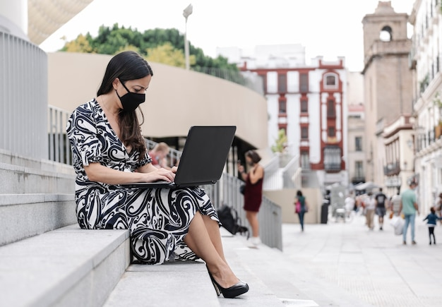 Businesswoman with a protective mask working with her laptop outside Premium Photo
