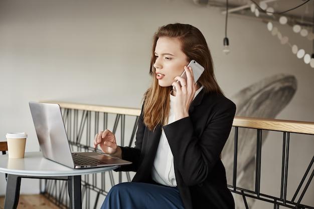 Donna di affari che lavora nella caffetteria, rispondere alle chiamate e guardando il laptop Foto Gratuite