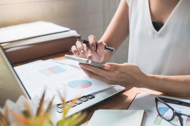 Businesswoman working on desk office with marketing graph statistics analysis Premium Photo