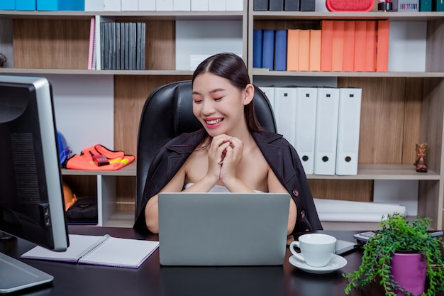 Businesswoman working in the office with a smile while sitting. Free Photo