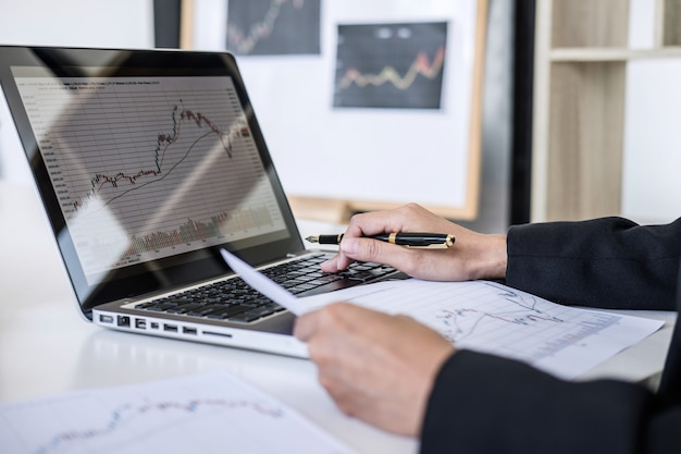 Businesswoman working with computer, laptop, discussing and analysis graph stock market trading Premium Photo