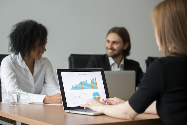 Businesswoman working with project statistics preparing report at team meeting Free Photo