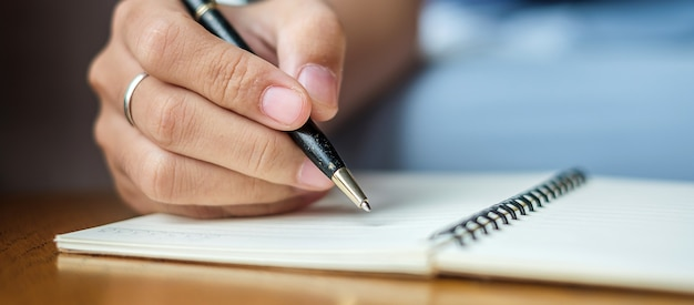 Businesswoman writing something on notebook in office Premium Photo