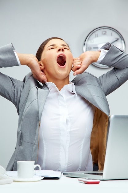 Businesswoman yawning in the office Free Photo