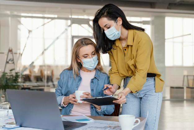 Деловые женщины в медицинских масках на работе Бесплатные Фотографии