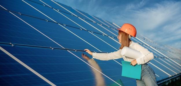 Businesswomen working on checking equipment at solar power plant with tablet checklist Premium Photo