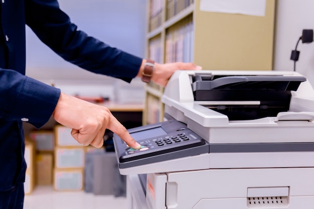 Bussiness man hand press button on panel of printer. Premium Photo