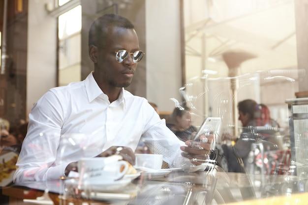 Деловые люди, современный городской образ жизни и технологии. красивый уверенно афроамериканский бизнесмен в sms оттенков и белой рубашке отправляя смс или проверяя электронную почту на мобильном телефоне во время перерыва на кофе в кафе Бесплатные Фотографии