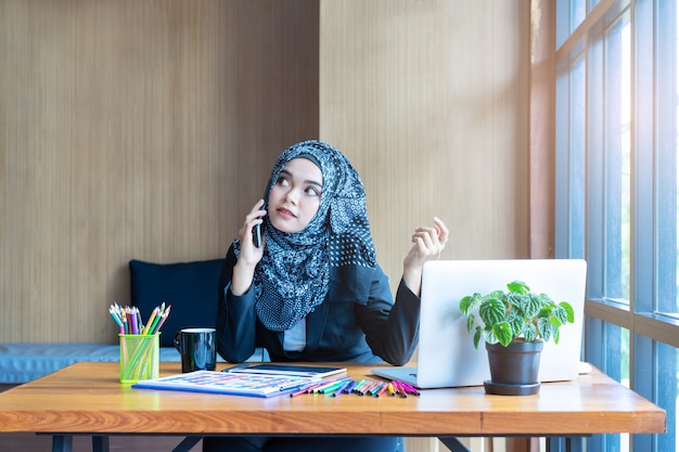 Busy asian muslim business woman talking on mobile phone in modern office. Premium Photo