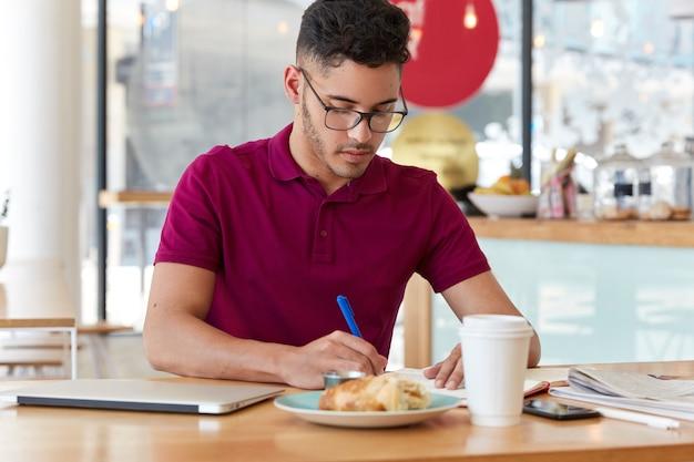 忙しいビジネスマンは眼鏡とtシャツを着て、メモ帳に情報を書き留め、スタートアッププロジェクトのアイデアを準備し、コーヒーを飲み、クロワッサンを食べ、ぼやけた壁に対してビストロでポーズをとります。 無料写真