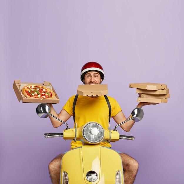 Занятый доставщик за рулем желтого скутера, держа коробки для пиццы Бесплатные Фотографии