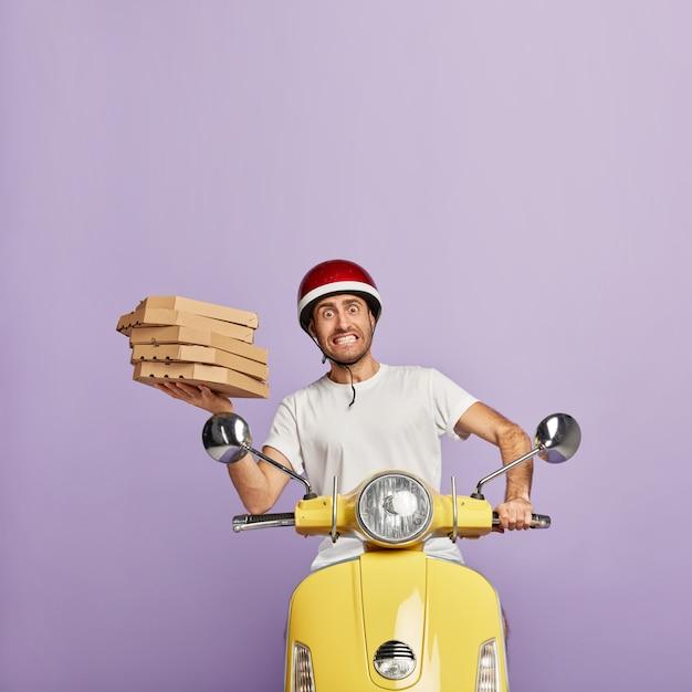 ピザの箱を持って黄色いスクーターを運転する忙しい配達員 無料写真