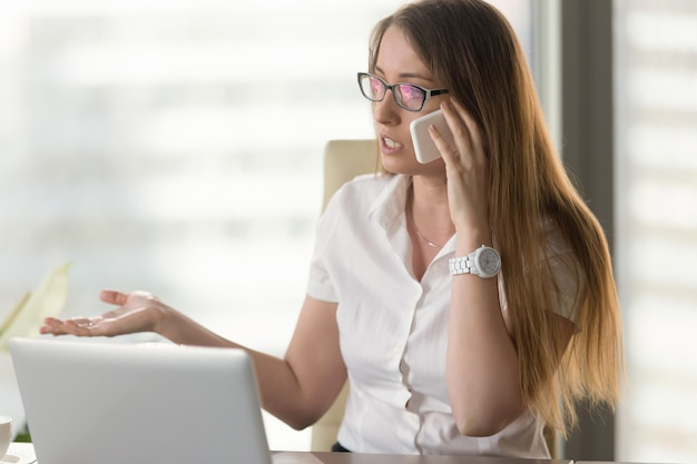 Busy female entrepreneur arguing by phone Free Photo
