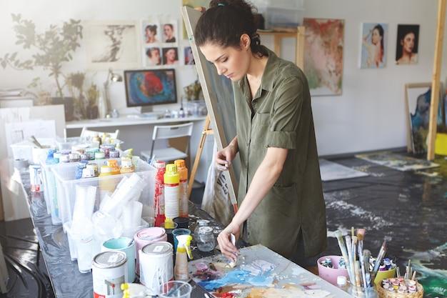 油でテーブルの近くに立って、アートスタジオで働いて、海の風景や肖像画を描くつもりで油絵の具を取る忙しい女性画家。ワークショップでキャンバスに取り組んでいる魅力的な若い女性 無料写真