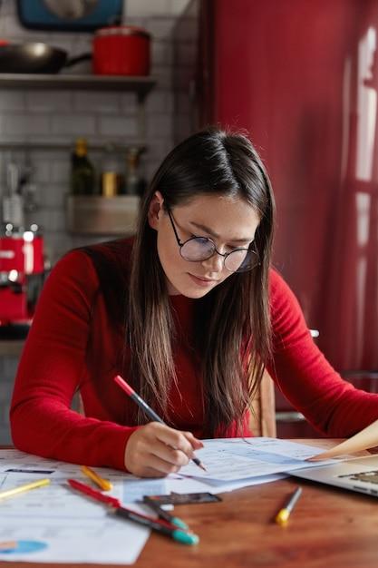 Занятая женщина думает о целевой или планирующей компании, проводит статистические или аналитические исследования, сидит за рабочим столом, на кухне. Бесплатные Фотографии