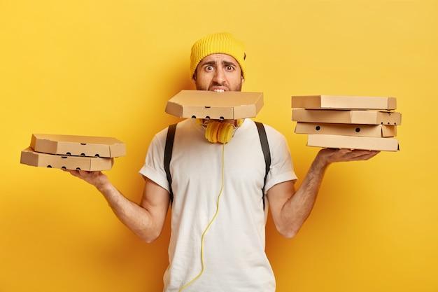 Un pizzaiolo impegnato e lavora sodo porta molte scatole di cartone con entrambe le mani e la bocca, ha molto lavoro, è un corriere professionale, indossa un cappello giallo e una maglietta bianca, offre uno spuntino delizioso per il cliente Foto Gratuite